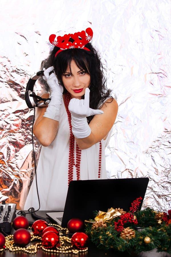 Le cuffie del costume di Santa del nuovo anno della donna del DJ argentano la parità del fondo fotografia stock