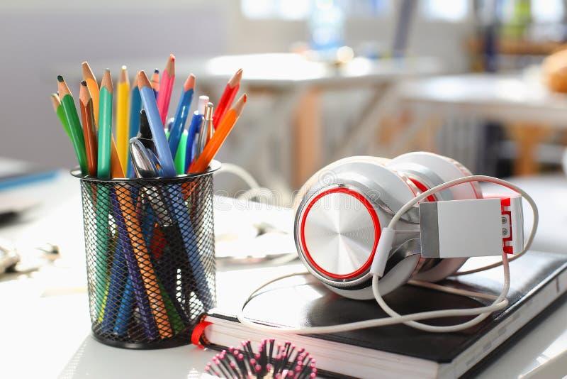 Le cuffie diario e matita si trovano sullo scrittorio del concetto immagine stock