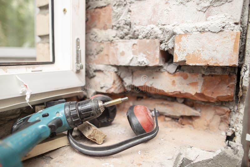 le cuffie funzionanti a prova di rumore e un cacciavite elettrico stanno trovando su un muro di mattoni vicino ad una finestra de immagini stock