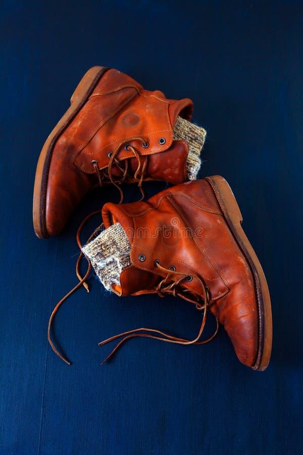 Le cuir bleu de fond de vue supérieure de vieilles chaussures rouge-brun de botte lace la toile élevée la laine que sale a tricot photo libre de droits