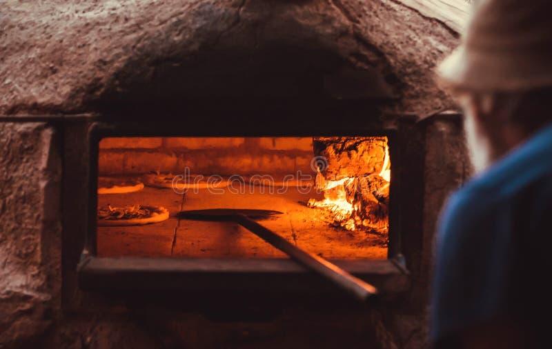 Le cuiseur met la pizza le four pour la cuisson restaurant italien traditionnel avec la pizza savoureuse photos stock