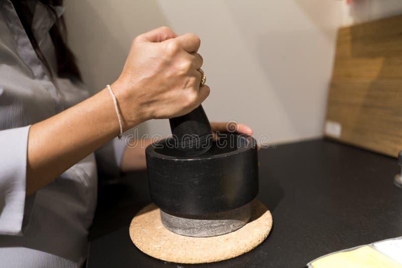 le cuiseur remet à broyage quelque chose utilisant le mortier et le pilon image libre de droits