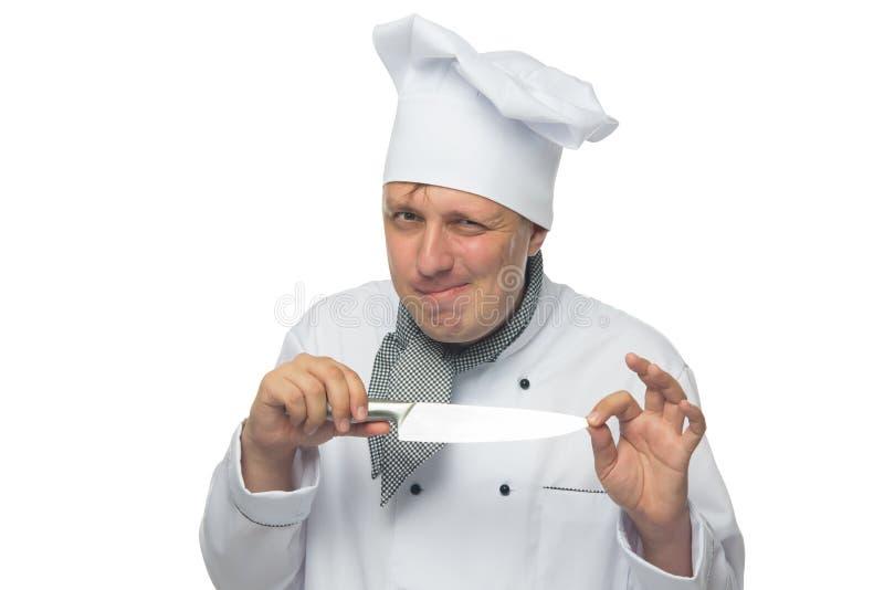 Le cuisinier adroit, sur un fond blanc, tient un couteau dans sa main photographie stock