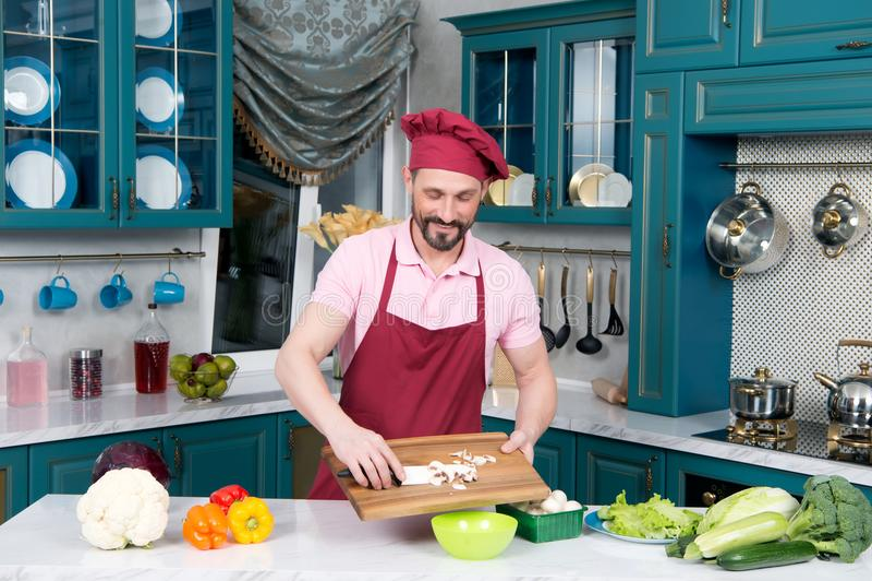 Le cuisinier barbu dans le tablier et le chapeau met des champignons de planche à découper boisée photo stock