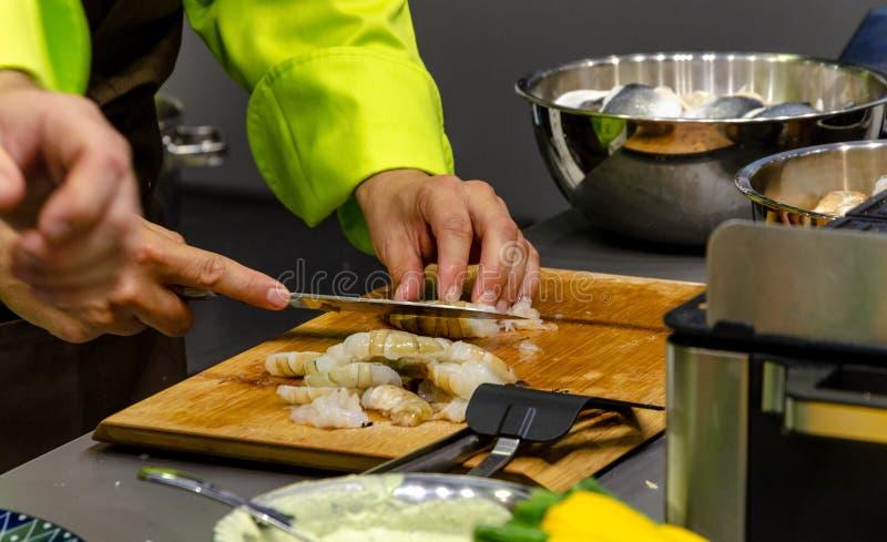 Le cuisinier coupe expert des crevettes roses de roi photo stock