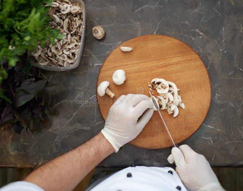 Le cuisinier coupe la vue de firstperson de cèpes images libres de droits