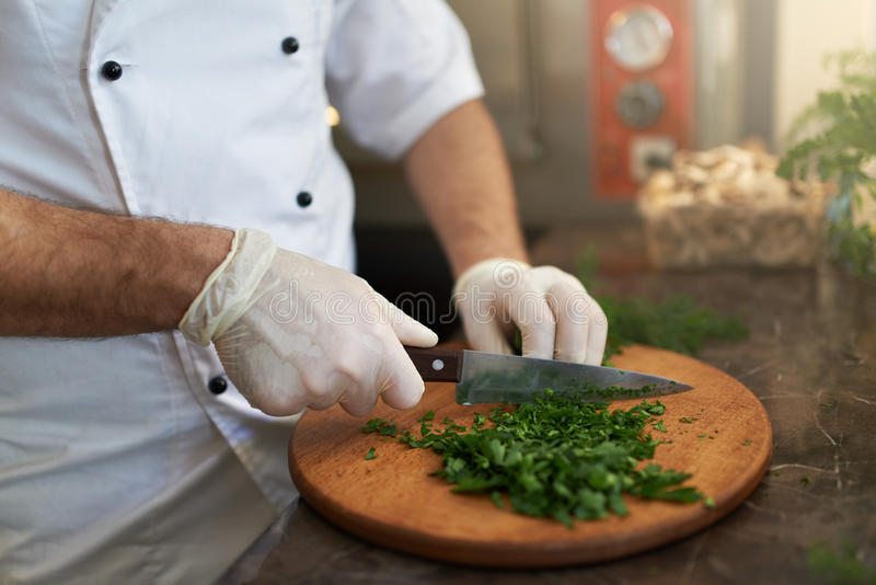 Le cuisinier coupe les herbes fraîches sur le conseil en bois photographie stock libre de droits