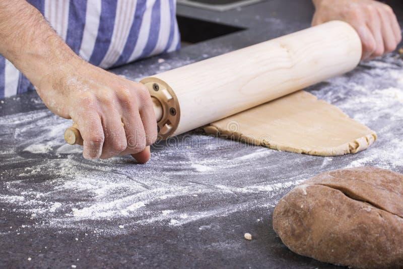 Le cuisinier déroule la pâte sur un panneau, la cuisson traditionnelle image libre de droits