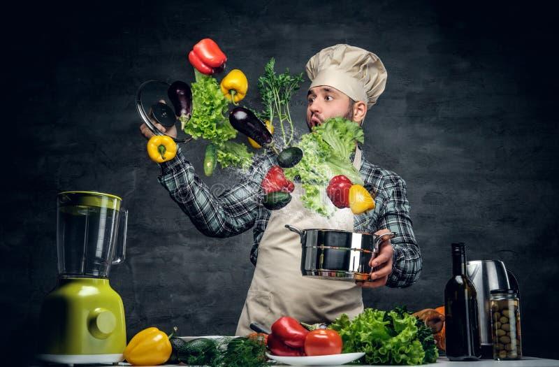 Le cuisinier d'homme tient une casserole avec des légumes volant dans le ciel photo stock