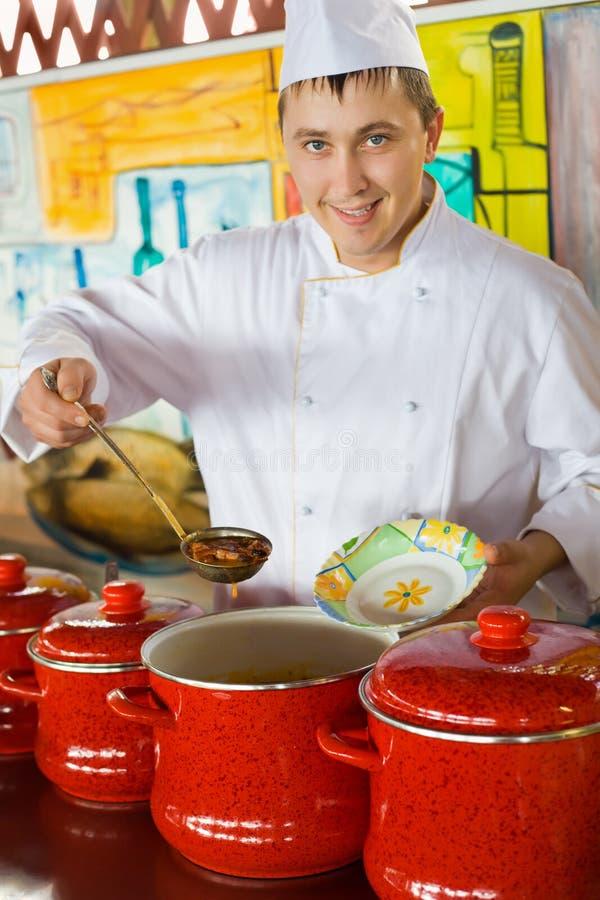 Le cuisinier dans la cuillère uniforme impose le potage dans la plaque photographie stock libre de droits