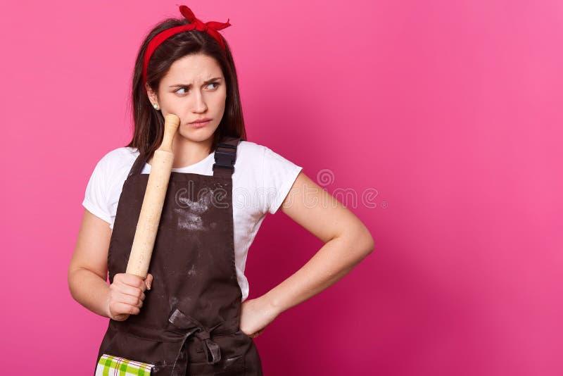 Le cuisinier de brune avec la bande rouge de cheveux, le tablier brun sali avec de la farine et le T-shirt blanc décide quelle re photographie stock