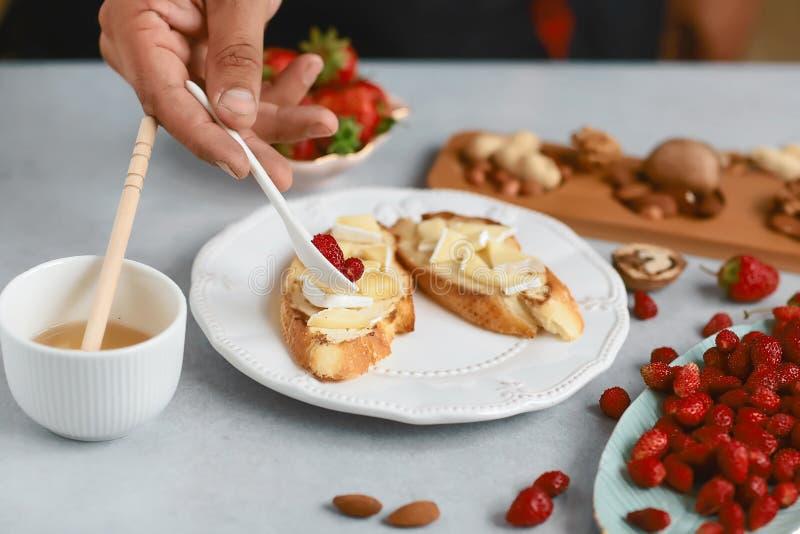 Le cuisinier de chef prépare les sandwichs doux avec les fraises, le fromage, le camembert, le brie, les écrous et le miel sur la photographie stock libre de droits
