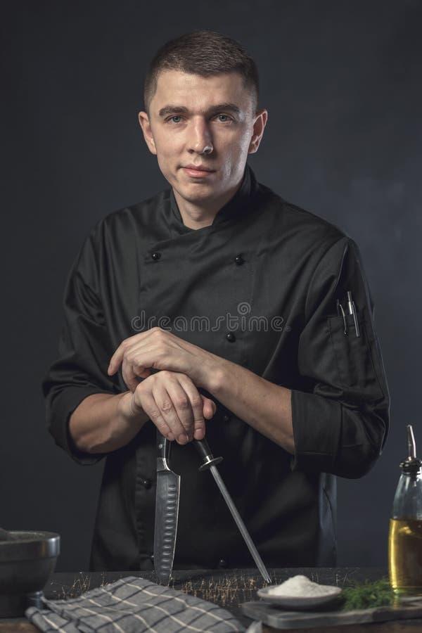 Le cuisinier de chef tient un couteau au-dessus de fond gris-foncé image libre de droits