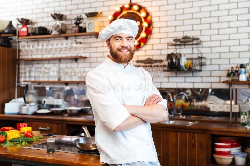 Le cuisinier de sourire de chef se tenant avec des mains s'est plié sur la cuisine photo stock