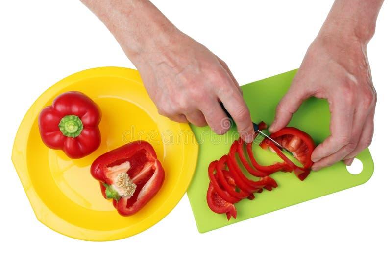 Le cuisinier en chef coupe le poivre rouge frais de paprika avec un couteau pointu image libre de droits
