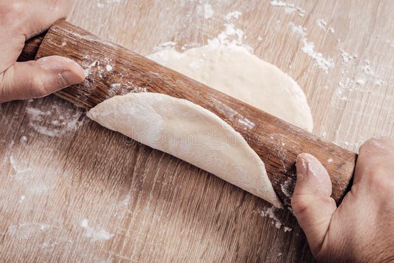 le cuisinier masculin déroule la pâte avec la goupille photo stock