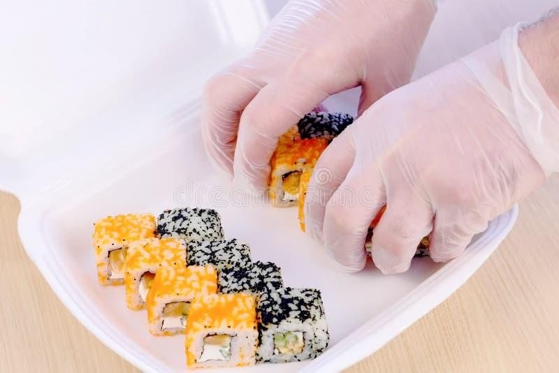Le cuisinier met des petits pains sur la boîte en plastique avec le wasabi et le gingembre pour la livraison dans le restaurant R photos libres de droits