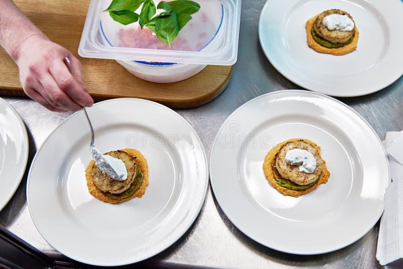 Le cuisinier met la crème sure dans le plat avec la côtelette de poissons photographie stock