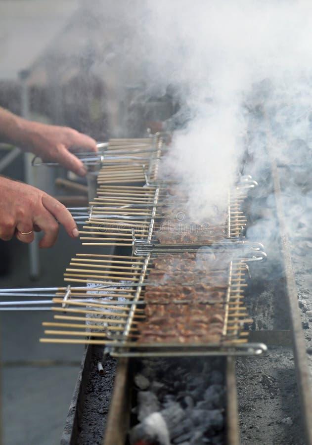Le cuisinier prépare des brochettes de viande grillée photos libres de droits