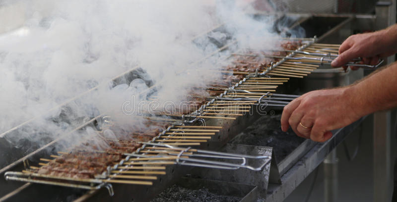 le cuisinier prépare des brochettes de viande grillée dans une stalle de nourriture de rue photographie stock libre de droits