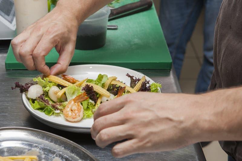 Le cuisinier prépare une salade de fruits de mer photos libres de droits