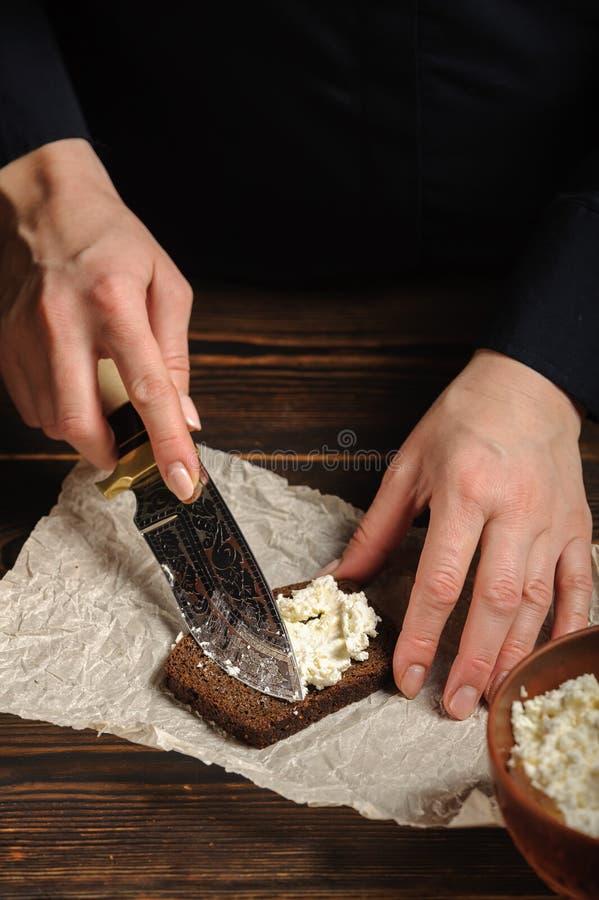 Le cuisinier répand le fromage blanc sur le pain images stock
