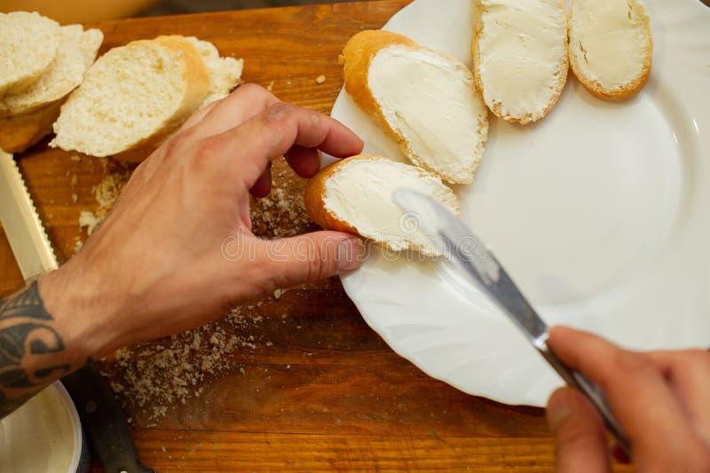 Le cuisinier r?pand le fromage blanc sur le pain images stock