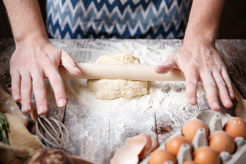 Le cuisinier roule la pâte sur la table avec une goupille photos libres de droits