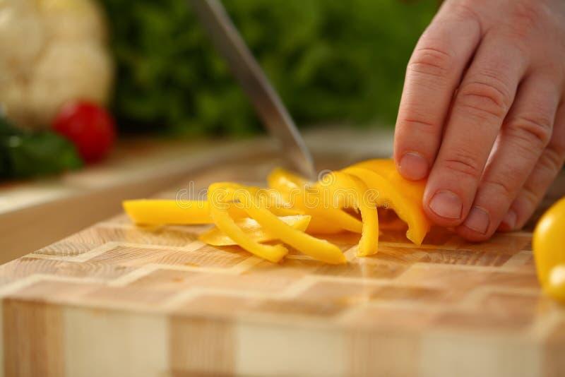Le cuisinier tient le couteau à disposition et les coupes dessus photographie stock