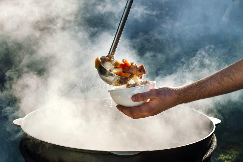 Le cuisinier verse la soupe dans une cuvette image libre de droits