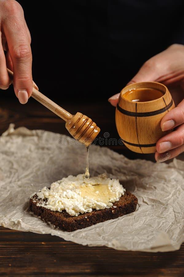 Le cuisinier verse le miel sur le pain photographie stock