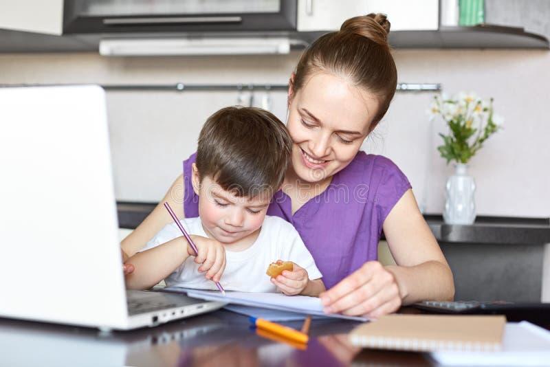 Le cure allegre della madre di suo figlio, essendo in congedo di maternità, impianti freelance insieme con il computer portatile, fotografia stock libera da diritti