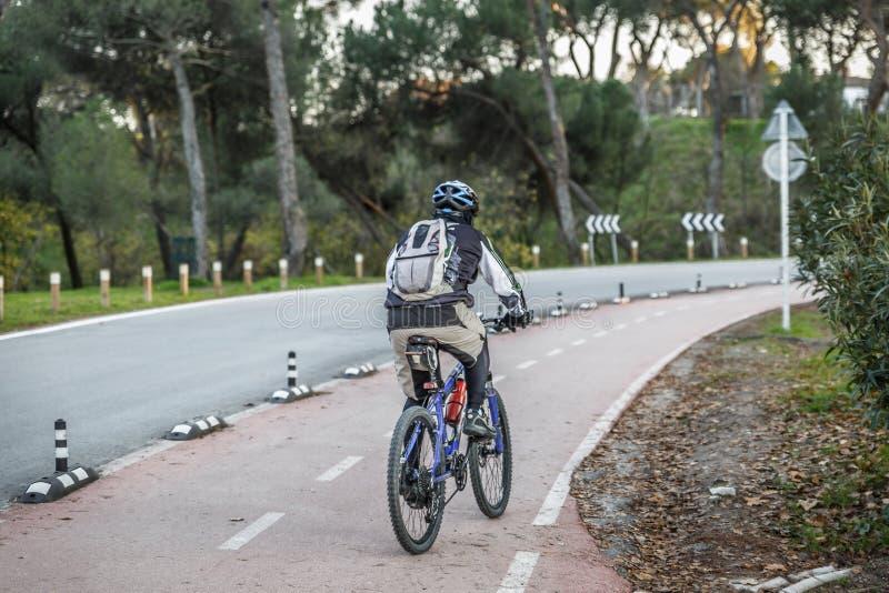 Le cycliste avec le sac à dos et le casque conduit un vélo de montagne dans une ruelle spéciale pour des cyclistes photos libres de droits