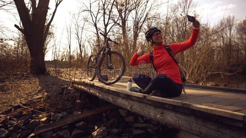Le cycliste caucasien heureux de femme fait ? une photo d'elle-m?me un selfie au t?l?phone tout en se reposant sur le pont au-des photos stock