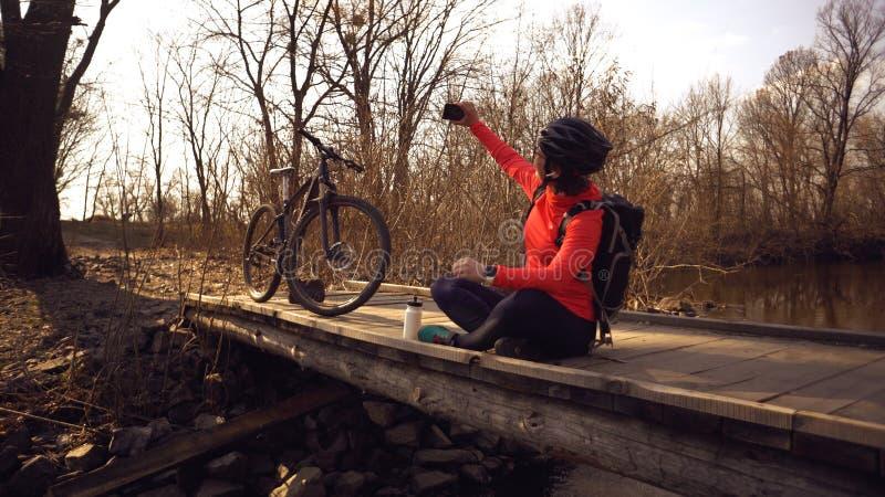 Le cycliste caucasien heureux de femme fait ? une photo d'elle-m?me un selfie au t?l?phone tout en se reposant sur le pont au-des photo stock