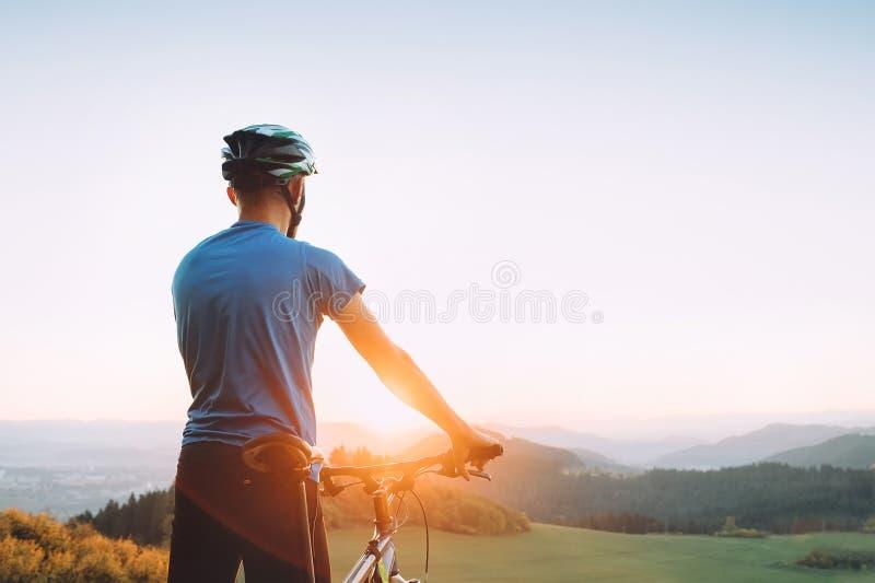 Le cycliste d'homme rencontre un coucher du soleil en montagne images stock