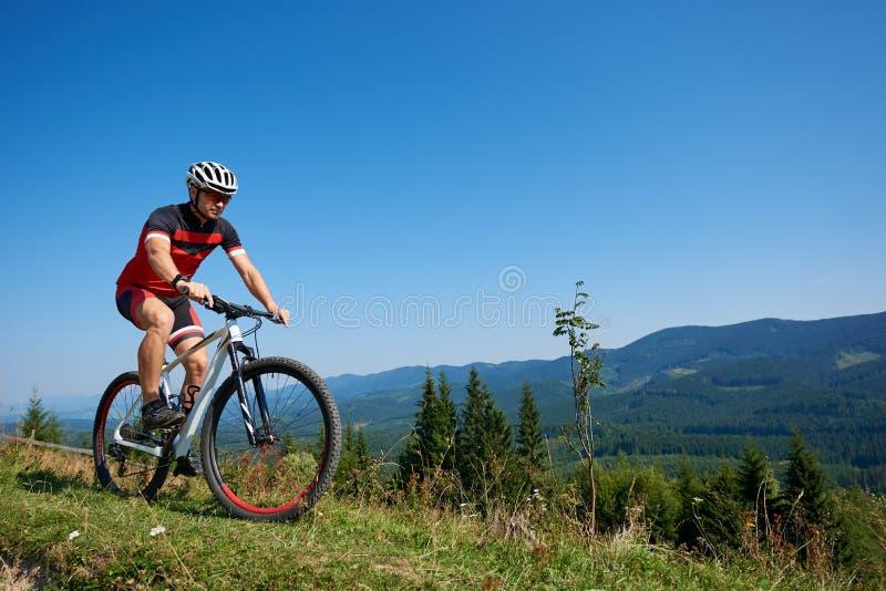 Le cycliste dans le casque, les lunettes de soleil et la pleine équitation d'équipement font du vélo sur la colline herbeuse image libre de droits