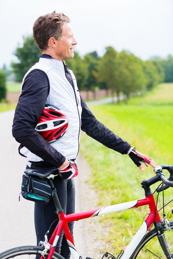 Le cycliste, descendu de son vélo, a le casque dans le bras photos stock
