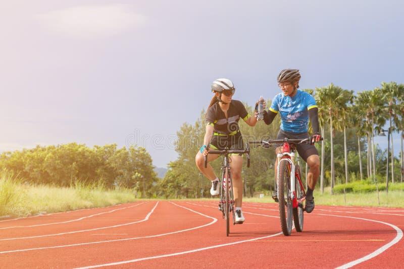 Le cycliste deux livrent l'eau potable en parc Sport de concept, confiance, ensemble, détente et travail d'équipe image libre de droits