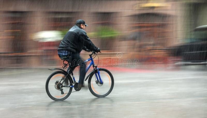 Le cycliste monte par les rues un jour pluvieux images stock