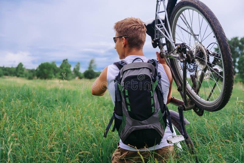 Le cycliste porte la bicyclette dans le pré vert images libres de droits