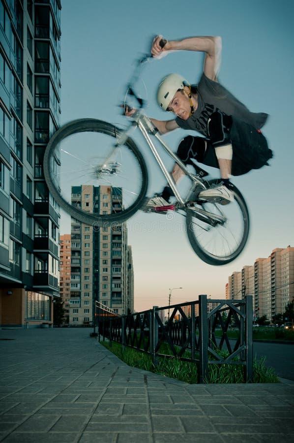 Le cycliste sautant par la frontière de sécurité photo stock