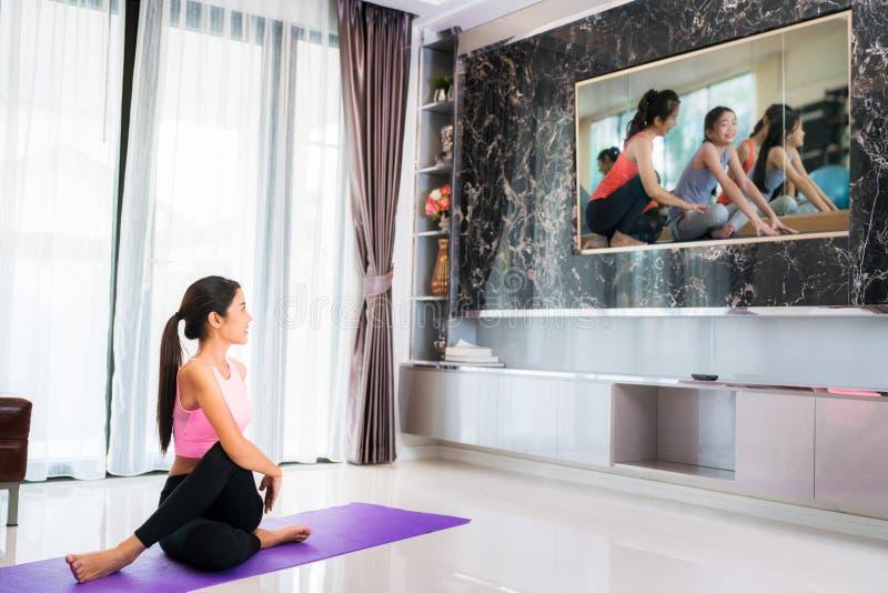 Le début asiatique de dame au yoga s'exerçant suivent par l'entraîneur dans la télévision photo libre de droits