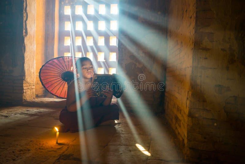 Le débutant non identifié de bouddhisme a lu un livre dans le temple de Buddihist images libres de droits
