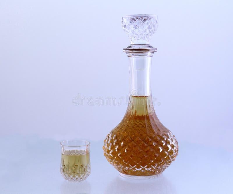 Le décanteur en cristal et le petit verre ont rempli de liquide d'or image libre de droits