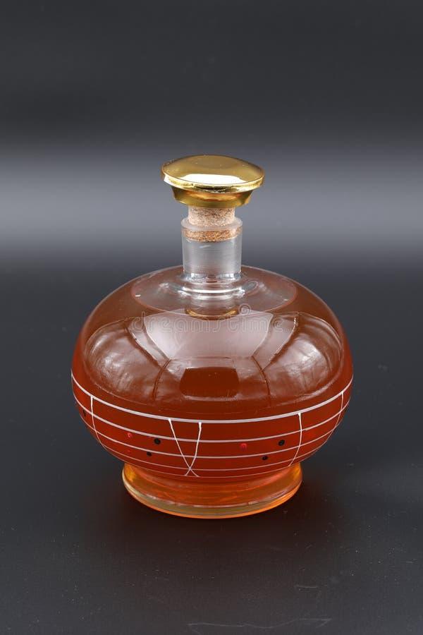 Le décanteur en verre rempli d'eau-de-vie fine et couvert de bouchon d'or photos stock