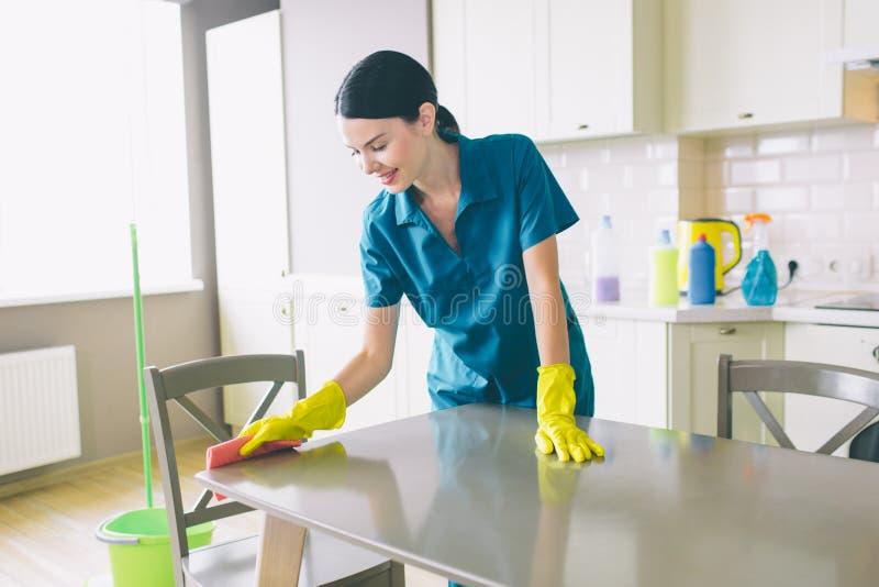 Le décapant soigneux et gentil se tient à la table et la nettoie Elle porte l'uniforme bleu et les gants jaunes La femme regarde  photos libres de droits