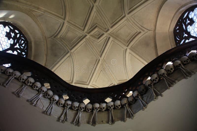 Le décor des crânes et des os humains dans un ossuaire du gothique de l'église de cimetière de tous les saints dans Kutna-Hora, R image stock