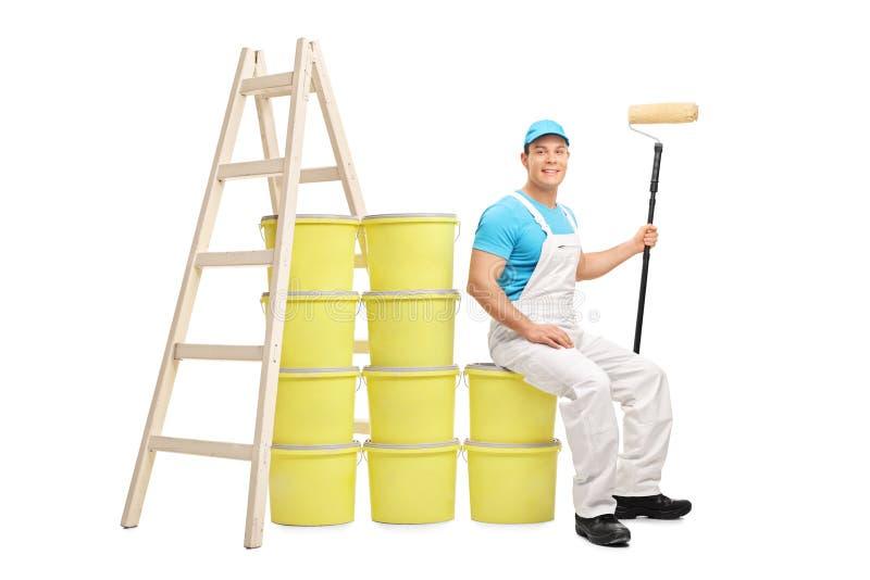 Le décorateur s'asseyant sur une pile de couleur buckets photo libre de droits