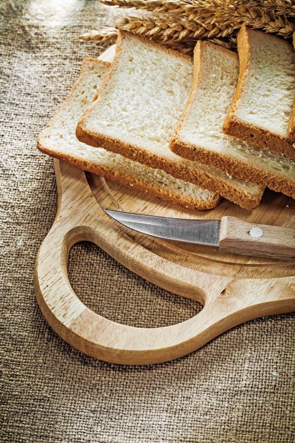 Le découpage du couteau de cuisine de conseil a découpé des oreilles en tranches de froment panifiable sur renvoyer b photographie stock libre de droits